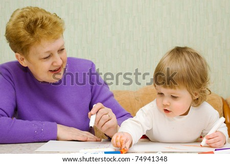 Small cute painting girl with grandma at home - stock photo