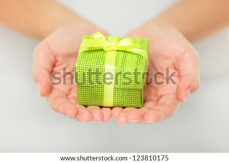 Small decorative colourful green gift held in outstretched cupped hands as a surprise Christmas present for a loved one - stock photo