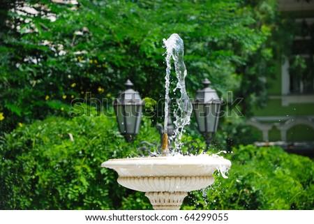 Small decorative fountain in a city park - stock photo