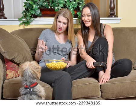 Small dog begging for popcorn from two female friends sitting on couch in living room of home - stock photo