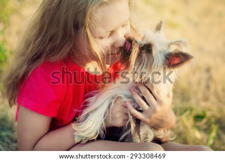 Small Doggie Licks a Girl's Face. Beautiful Happy Teenager with Long Fair Hair and Her Pet - stock photo