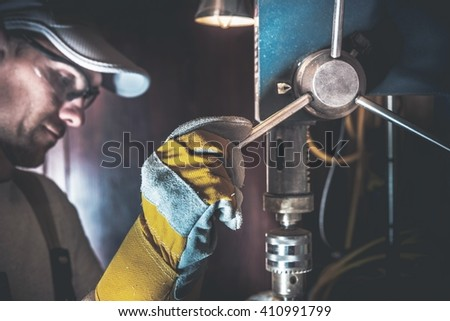 Small Drill Works in a Garage. Caucasian Men Using Metal Driller Machine. - stock photo