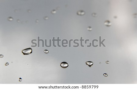 Small droplets on a reflective gray metallic surface