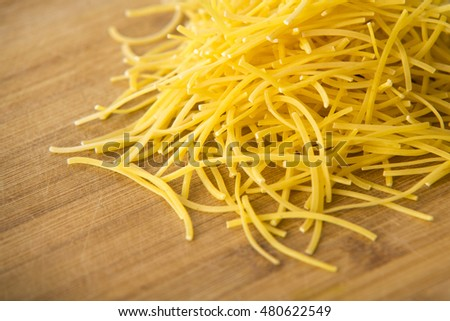Small dry pasta noodles on wood background