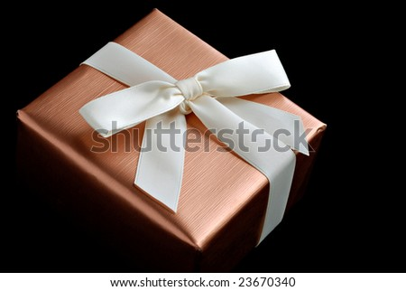Small elegantly wrapped gift box with ribbon on black background.  Macro with shallow dof. - stock photo