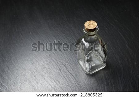 small empty bottle on a black slate - stock photo