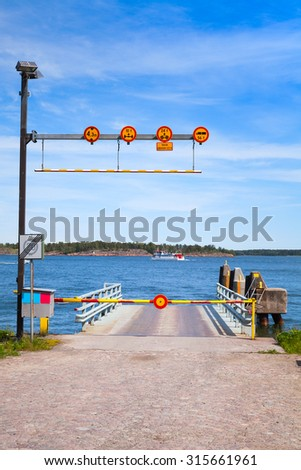 Small empty ferry terminal with metal ramp, cosed turnpike and roadsigns - stock photo