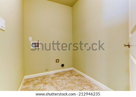 Small empty laundry with tile floor - stock photo