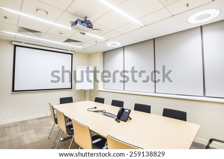 Small empty meeting room with TV projector and flipchart - stock photo