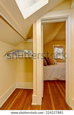 Small empty walk in closet interior with vaulted ceiling and skylight.