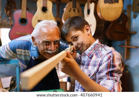 Small family business and traditions: old grandpa with grandson in lute maker shop. The senior artisan teaches to the boy how to chisel wood to make a music instrument.  - stock photo