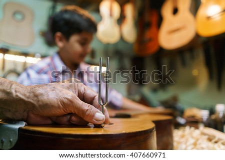 Small family business and traditions: old grandpa with grandson in lute maker shop. The senior artisan teaches how to tune a classic guitar to the boy. Closeup of hand holding a diapason  - stock photo