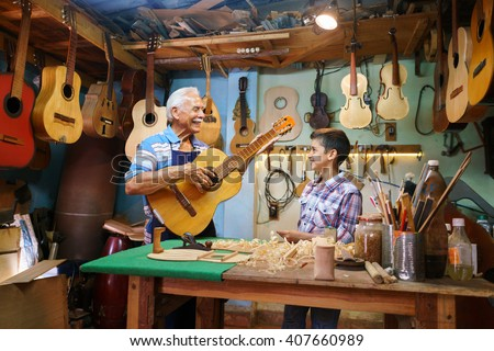 Small family business and traditions: old grandpa with grandson in lute maker shop. The senior artisan gives teaches how to play classic guitar to the boy, who looks carefully at the instrument - stock photo