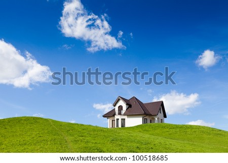 Small family house on green field with blue sky - stock photo