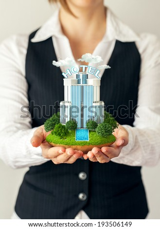 Small fantastic island with a hotel in businesswomen's hands. - stock photo