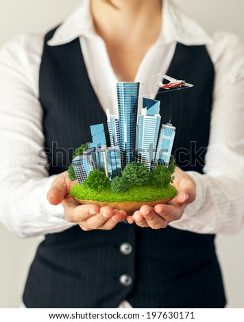 Small fantastic island with a modern city in women's hands. - stock photo