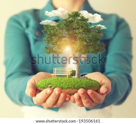 Small fantastic island with a tree in women's hands. - stock photo