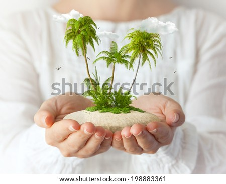 Small fantastic island with  palms in women's hands. Tropical vacation - stock photo