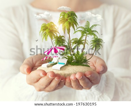 Small fantastic island with sunbeds and palms in women's hands. Tropical vacation - stock photo