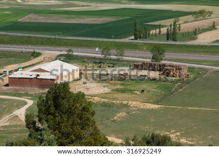 small farm and horse stables in the field - stock photo