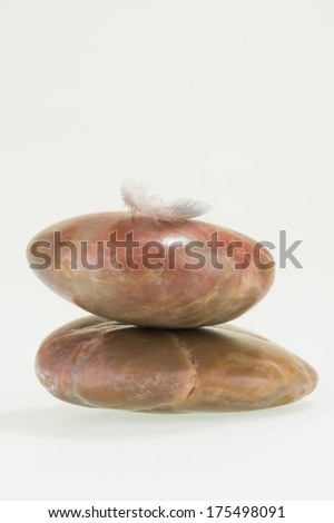 Small feather balancing on red river stones close up - stock photo