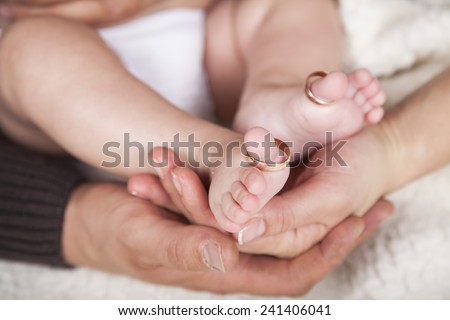 Small feet baby holds his mother in her hands. with the wedding rings in baby toe. - stock photo