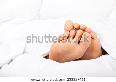 Small female feet under bed sheet. - stock photo