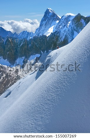 small figure of a man and the high peaks of the Swiss Alps - stock photo