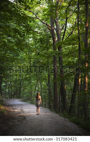 Small figure of young woman standing on path in dark forest with big tall trees illuminated by evening sunshine - stock photo