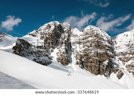 Small figures of skiers and the big mountain, the Asutrian Alps - stock photo