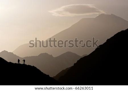 Small figures on the mountain range, Caucasus Mountains, Elbrus - stock photo