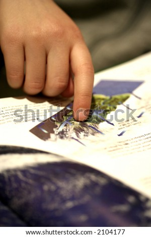 Small finger of a child pointing to an information in a book. - stock photo