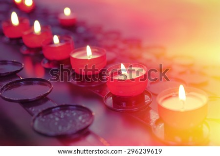Small firing candles in catholic church on dark background. Filtered photo with effects