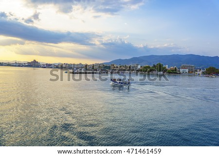 Small fish boat travelling in the port against a blue cloudy sky in Kalamata - Greece.