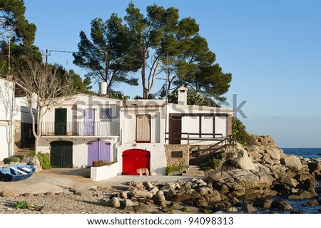 Small fishermen bay at Costa Brava, Catalonia with colorfully painted wooden doors - stock photo
