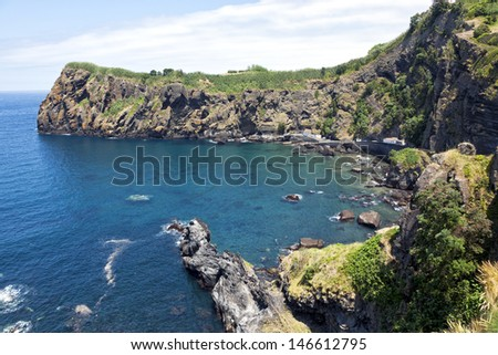 Small fishery harbor at the bay of Capelas on the northern coast of Sao Miguel - stock photo