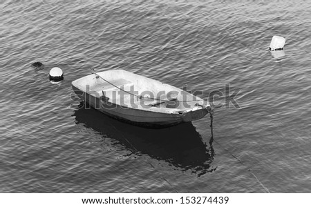 Small fishing boat floating in the fish port of Cascais - Portugal (black and white) - stock photo