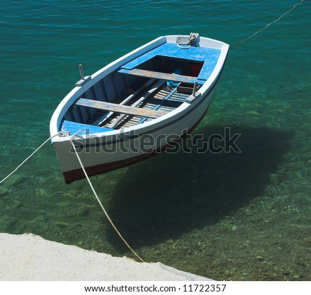 Small fishing boat floating on the water - stock photo
