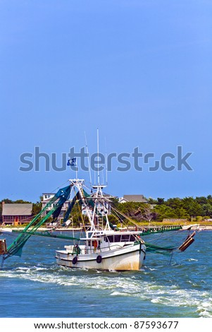 small fishing boat heading out to the ocean - stock photo