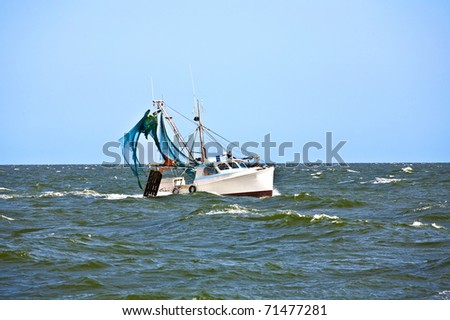 small fishing boat heading out to the ocean in late afternoon - stock photo