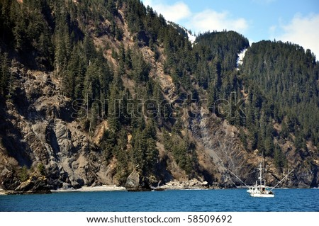 Small fishing boat in Alaska near a cliff - stock photo