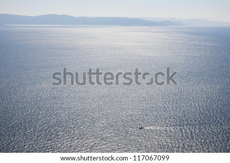 Small fishing boat in morning light outside the the Spanish west coast on the Atlantic Ocean. - stock photo
