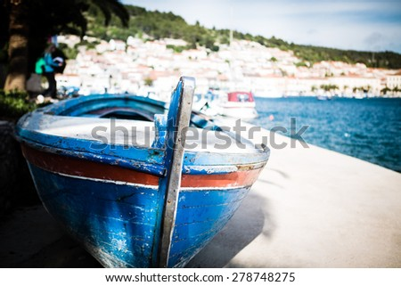 Small fishing boat on sunny morning in Vela Luka,Korcula Island, Croatia.A photo of small fishing boat an early sunny morning.Small rowboat anchored at shore - stock photo