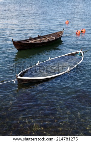 Small fishing boat sinking to the sea - stock photo