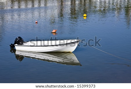 Small fishing boat with beautiful reflection. - stock photo