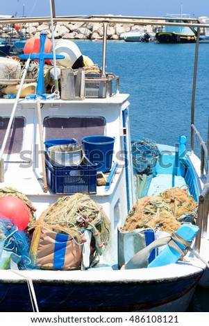 Small fishing boat with nets and other equipment in harbour, Greece
