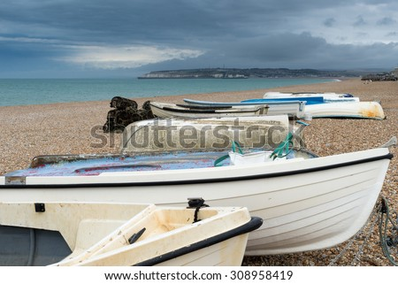 Small fishing boats on a beach under stormy skies.