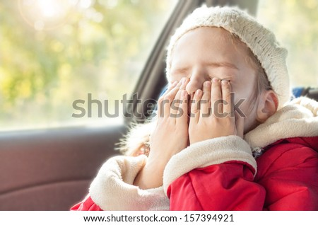 Small five years old caucasian girl in warm clothes crying while traveling in a car seat - close up autumn portrait - childhood - stock photo