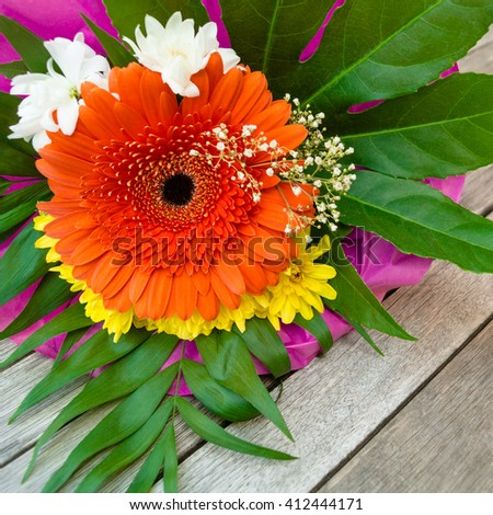 Small flower bouquet of orange, white and yellow blossoms and green leaves on wooden ground - stock photo