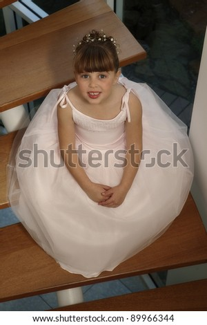 Small flower girl sits on the steps after the wedding - stock photo